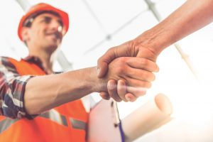 Construction worker in hard hat and vest shaking hands holding papers