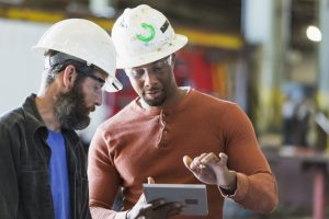 two manufacturing workers with tech tablet
