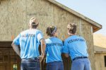 Volunteers from a home service company help build a home