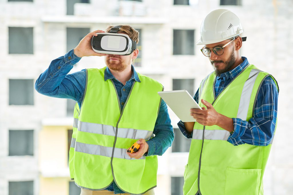 Two construction workers utilize technology, a tablet and a VR headset, to accomplish their tasks and make their jobsite safer.
