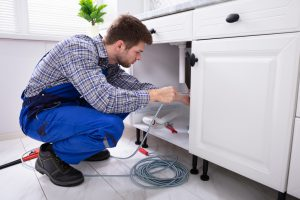 Home service expert repairs clogged drain