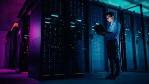 male IT technician working on laptop in server room