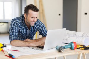 Construction manager uses computer to do content marketing