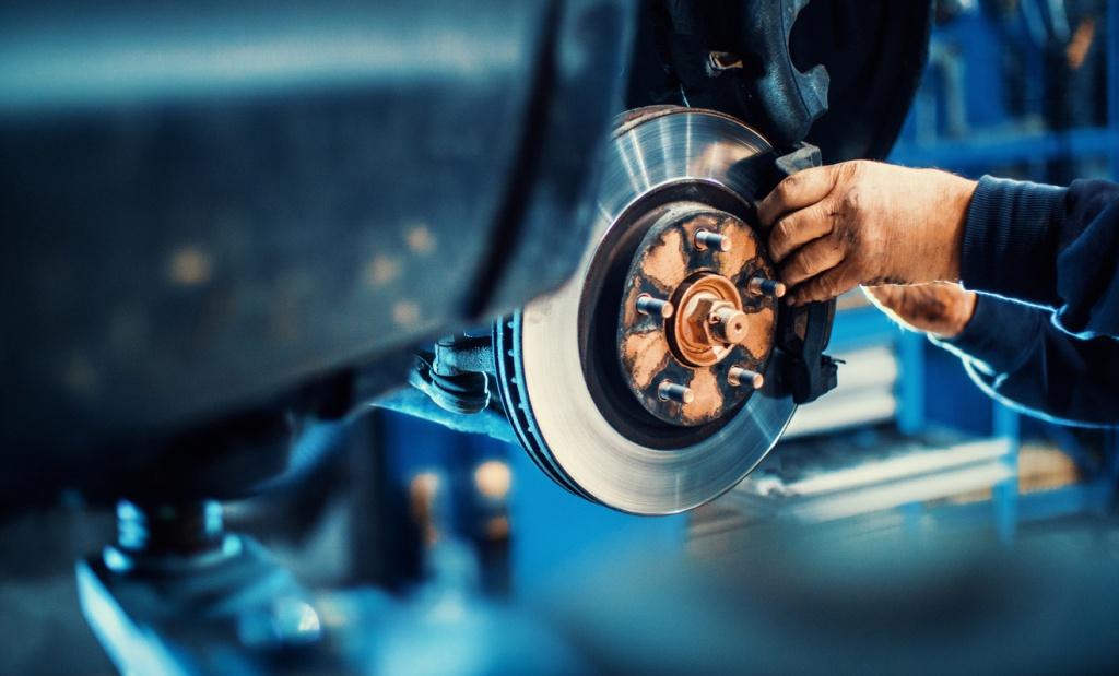 Closeup of unrecognizable mechanic replacing car brake pads
