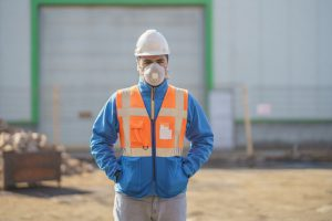 Manufacturing worker stands outside with mask