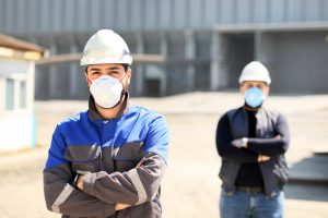 Two construction workers wear masks and distance themselves from each other