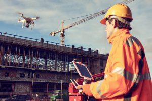 Construction worker flies a drone over a high-technology jobsite
