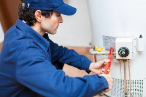 Plumbing professional repairing a water heater.