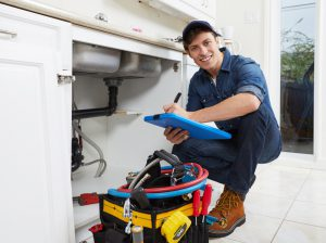 Plumber from a home service franchise checks underneath a sink