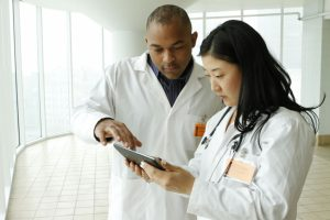 Female Asian doctor with African American doctor looking over charts on tablet