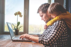 Father working on laptop as son hugs him